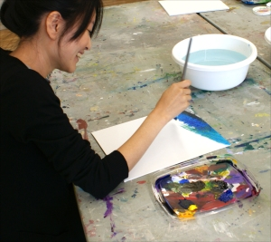 a student paints during a class